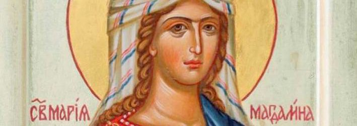 Beautiful icon of Mary Magdalen. She is wearing a blue robe around a yellow-gold top that has beautiful red embroidery at the top. She is holding a large red Easter Egg in her right hand, and carrying a decorated red vessel (about the same size as the large egg), presumably containing myrrh. Her hair is in gold braids that come down past her shoulders, and are partially visible underneath her white headdress with blue and white stripes.