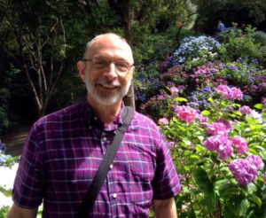 Fr. Nick in a garden in Wellington, New Zealand, wearing a short-sleeved purple shirt with purple rhododendrons in the background.